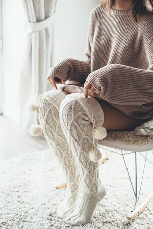 Cold autumn or winter weekend while relaxing on rocking chair. Cold lazy day in knitted socks and sweater at home. Cosy scene, hygge concept.