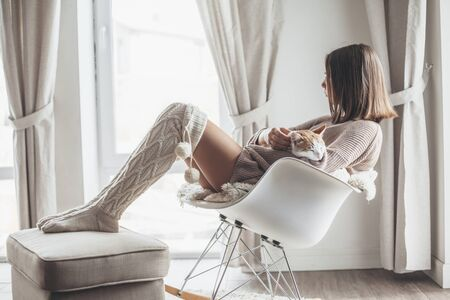 Owner playing with cat one winter weekend. Girl dressed in knit woolen sweater relaxing with her pet on a rocking chair in scandinavian home. Cosy scene, hygge concept.