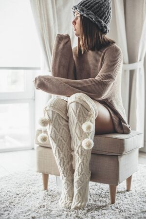 Cold autumn or winter weekend while relaxing in warm home clothing. Cold lazy day in knitted socks and sweater. Cosy scene, hygge concept. Zdjęcie Seryjne