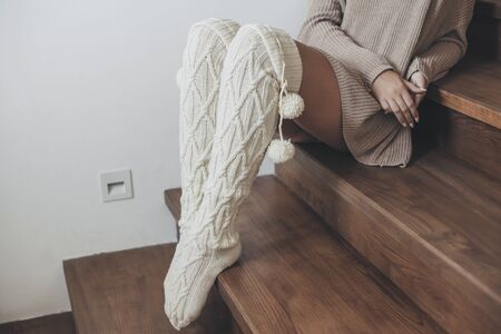 Girl in woolen knitted socks and sweater sitting on stairs at scandinavian home. Cosy scene, hygge concept. Zdjęcie Seryjne