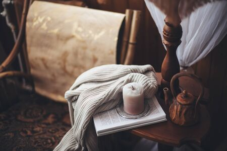 Book, candle, teapot and sweater on coffee table near armchair in wooden house. Cozy place for reading and resting at home.