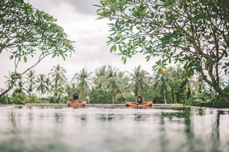 Young couple swimming in infinity pool with in private villa resort. Travelling to Ubud, Bali. Zdjęcie Seryjne