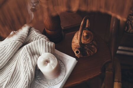 Book, candle, teapot and sweater on coffee table in wooden house. Cozy place for reading and resting at home.