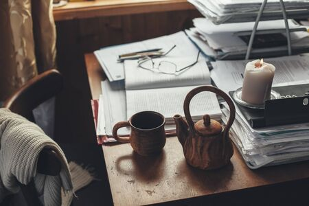Cozy home office in wooden house. Drinking tea while working with papers.