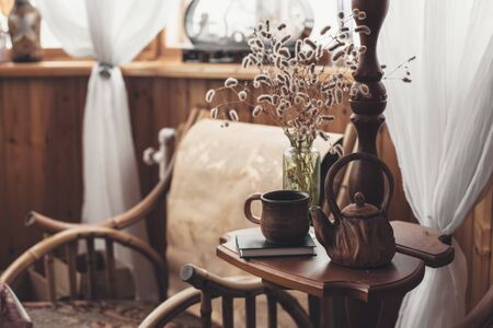 Book, vase and teapot on coffee table near armchair in wooden house. Cozy place for reading and resting at home some autumn weekend.
