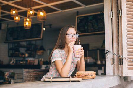 Jovencita positiva disfrutando de un batido dulce mientras pasa tiempo en la cafetería loft