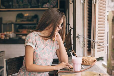 Positive teen girl using smartphone and enjoying sweet smoothie while spending time in loft cafe