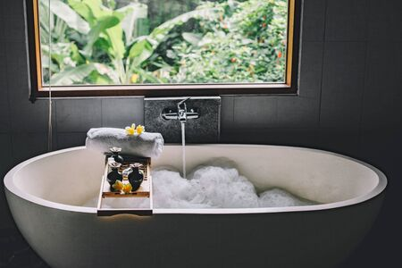 Beauty products on tray on bathtub by the window. Bath with foam is filling with water. Relaxing in Bali luxury spa hotel.