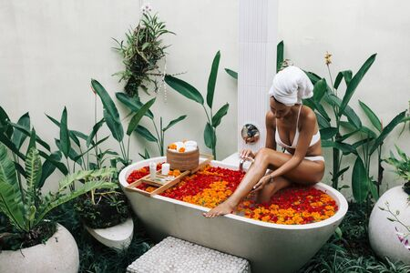 Woman with wrapped towel on head is applying oil to her legs in outdoor bath with flowers in Bali spa hotel.
