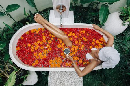 Woman with wrapped towel on head is drinking tea or coffee while relaxing in outdoor bath with flowers in Bali spa hotel, top view from above.