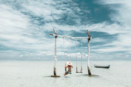 Girl hanging on swing on tropical beach on paradise Bali island Фото со стока