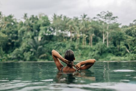 Happy woman enjoying warm tropical rain falling on her while swimming in infinity pool with a jungle view in Ubud, Bali