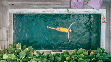 Teen girl relaxing at pool on Bali private villa, top view from above Фото со стока