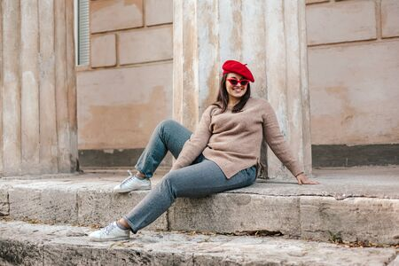 Plus size fashion model wearing simple sweater, red beret and chic sunglasses posing in the old city street in autumn. Stylish fall clothing for beautiful and happy overweight woman.