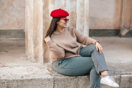 Modelo de talla grande con suéter simple, boina roja y elegantes gafas de sol posando en la calle de la ciudad vieja en otoño. Ropa de otoño elegante para mujer hermosa y feliz con sobrepeso.