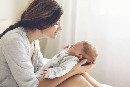 Loving mom carying of her newborn baby at home. Bright portrait of happy mum holding infant child on hands. Mother hugging and kissing her little 2 months old son.