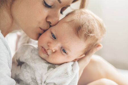 Loving mom carying of her newborn baby at home. Mother kissing her little 2 months old son. Фото со стока - 131725378