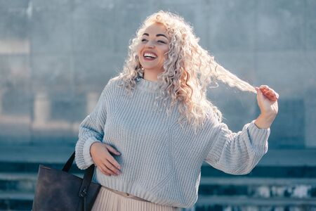 Beautiful plus size model with blond curly hair wearing grey knitted sweater and pastel skirt posing on city street. Fashion everyday outfit for cold season. Фото со стока - 131818778