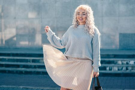 Beautiful plus size model with blond curly hair wearing grey knitted sweater and pastel skirt posing on city street. Fashion everyday outfit for cold season. Фото со стока - 131815203