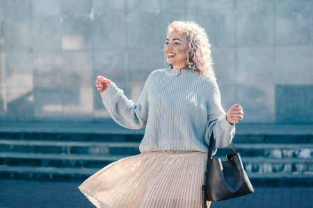 Beautiful plus size model with blond curly hair wearing grey knitted sweater and pastel skirt posing on city street. Fashion everyday outfit for cold season.