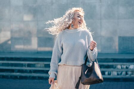 Beautiful plus size model with blond curly hair wearing grey knitted sweater and pastel skirt posing on city street. Fashion everyday outfit for cold season. Фото со стока - 131820100
