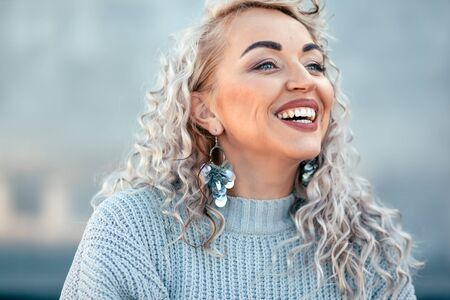 Beautiful plus size model with blond curly hair wearing grey knitted sweater and silver earrings posing on city street. Fashion everyday outfit for cold season.