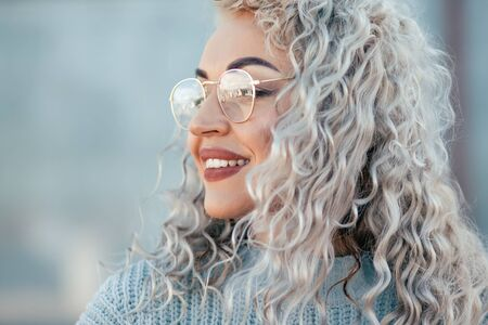 Beautiful plus size model with blond curly hair wearing grey knitted sweater and hipster glasses posing on city street. Fashion everyday outfit for cold season.
