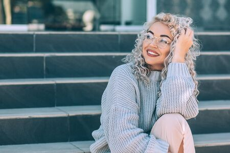 Beautiful plus size model with blond curly hair wearing grey knitted sweater and hipster glasses posing on city street. Fashion everyday outfit for cold season. Фото со стока - 131807131