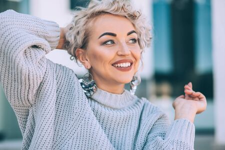 Beautiful plus size model with blond curly hair wearing grey knitted sweater and silver earrings posing on city street. Fashion everyday outfit for cold season. Фото со стока - 131807839
