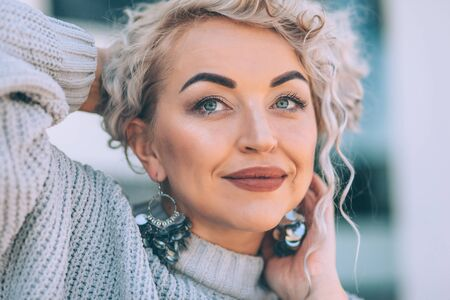 Beautiful plus size model with blond curly hair wearing grey knitted sweater and silver earrings posing on city street. Fashion everyday outfit for cold season. Фото со стока - 131807708