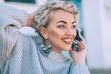 Beautiful plus size model with blond curly hair wearing grey knitted sweater and silver earrings posing on city street. Fashion everyday outfit for cold season. Фото со стока - 131807651