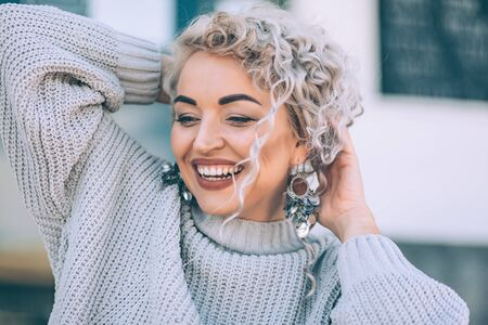 Beautiful plus size model with blond curly hair wearing grey knitted sweater and silver earrings posing on city street. Fashion everyday outfit for cold season. Фото со стока - 131808067