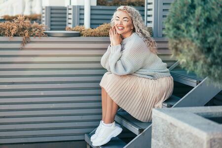 Beautiful plus size model with blond curly hair wearing grey knitted sweater and hipster glasses posing on city street. Fashion everyday outfit for cold season. Фото со стока - 131815278