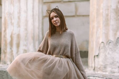 Sepia filtered photo of teen girl wearing brown tulle skirt and knitted oversized sweater posing in city street. Фото со стока