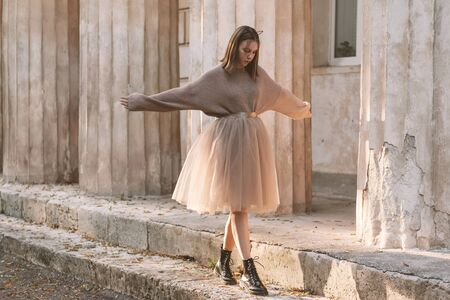 Sepia filtered photo of teen girl wearing brown tulle skirt, knitted oversized sweater and leather boots posing in city street. Фото со стока