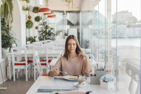 Cute teen girl eating tasty dessert while spending time in bright cafe Фото со стока - 131820277