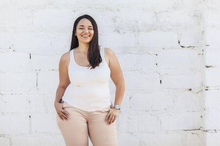 Bellissimo modello femminile plus size vestito con camicia bianca vuota in posa su sfondo muro di mattoni