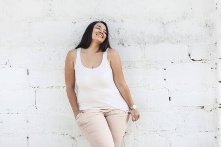 Beautiful plus size female model dressed in blank white shirt posing over brick wall background 스톡 콘텐츠 - 132525092