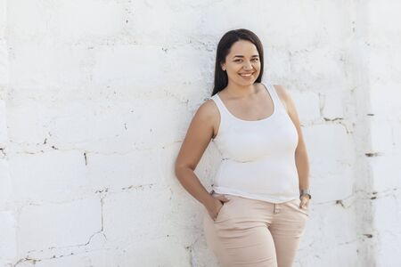 Beautiful plus size female model dressed in blank white shirt posing over brick wall background