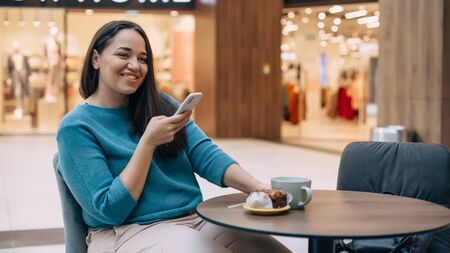 Beautiful plus size woman using mobile phone and eating dessert with coffe while resting in cafe inside city mall Фото со стока