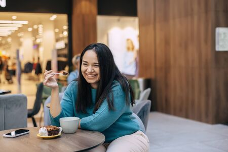 Beautiful plus size woman eating dessert with coffe while resting in cafe inside city mall Фото со стока