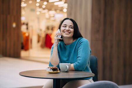 Beautiful plus size woman talking by mobile phone and eating dessert with coffe while resting in cafe inside city mall Фото со стока