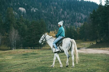 Teen girl riding a white horse on meadow by forest in nature Imagens