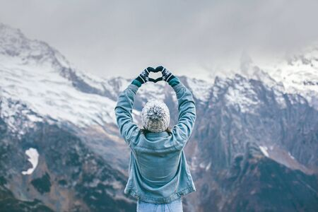 Back view of young traveler girl in gloves and hat standing over snowy mountain peaks and making shape of love heart by hands. Winter traveling scene, wanderlust concept.