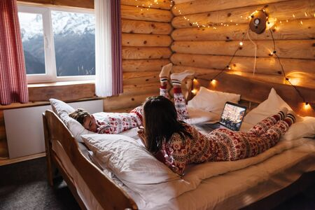 Dreamy Christmas vacation in log house with winter mountains landscape in window. Two teen friends wearing same traditional pajamas watching movie while relaxing in bed inside cozy cabin in the evening.