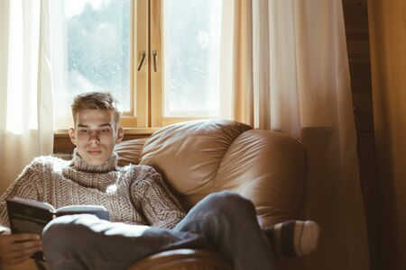 Young man in warm sweater reading book while relaxing on armchair by the window inside cozy log cabin