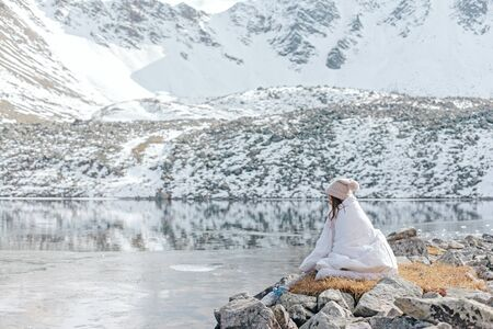 Young girl covered in blanket relaxing in wild nature with a view on beautiful landscape in cold season. Dreamy wanderlust concept scene. Spending perfect winter vacations by lake in mountains.