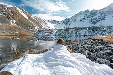 Young girl relaxing in comfy bed in wild nature with a view on beautiful landscape in cold season. Dreamy wanderlust concept scene. Spending perfect winter vacations by lake in mountains. 版權商用圖片