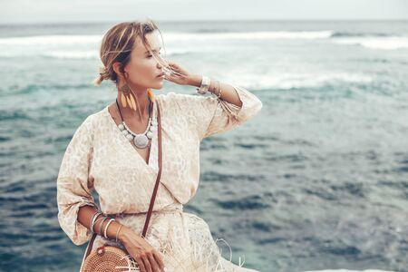 Modelo de estilo boho con vestido, aretes de plumas y bolso en la playa en Bali Foto de archivo