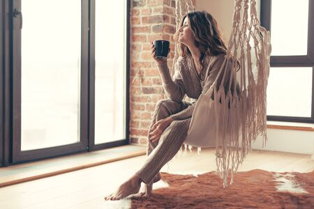 Beautiful young woman, which is wearing cashmere nightwear clothes, drinking tea or coffee while relaxing on rocking chair in scandinavian cabin near big window one lazy weekend morning Archivio Fotografico